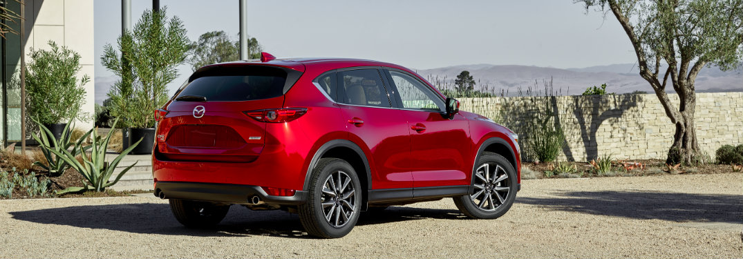 rear view of red 2018 mazda cx-5 on gravel driveway of modern home