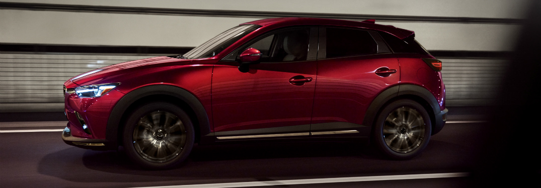 side view of red 2019 mazda cx-3 driving through tunnel