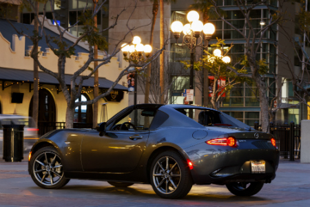 side and rear view of silver 2018 mazda miata rf under city lights at night