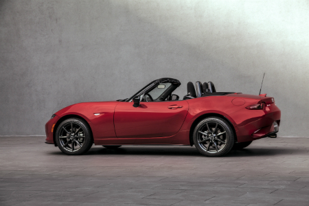side view of red 2018 mazda miata in front of gray stone wall