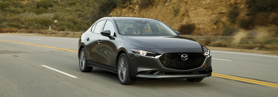 Grey 2019 Mazda3 driving by a hilly area