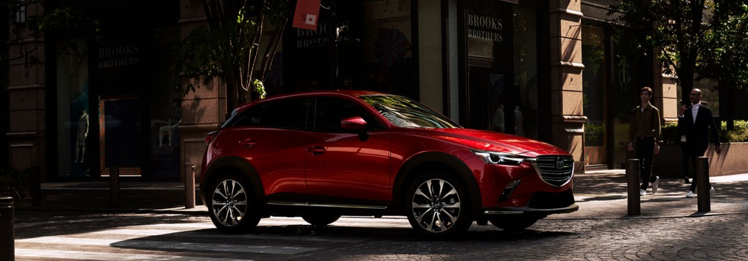 Two men stand next to a red 2019 Mazda CX-3