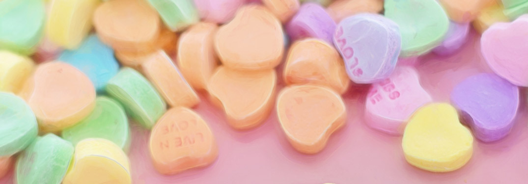 A pile of candy hearts over a pink background