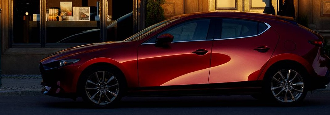 2019 Mazda3 parked in front of a large building at dawn
