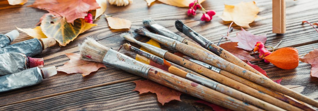 A set of brushes and leaves on a wooden table