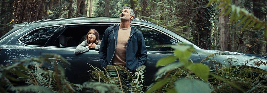 A man and young girl looking at the sky from a 2020 Mazda CX-9