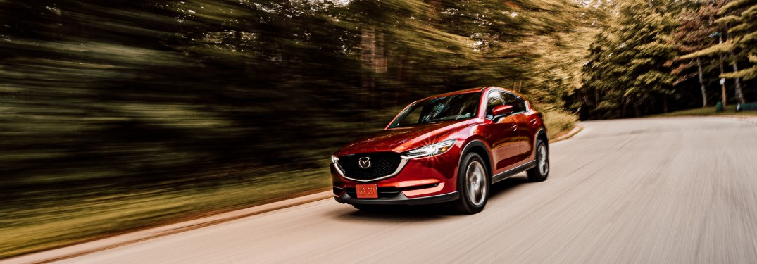 A red 2020 Mazda CX-5 driving quickly down a road.