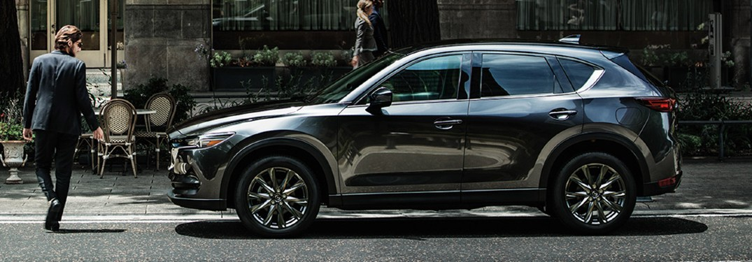 A gray 2020 Mazda CX-5 parked in a city road with a man walking in front of it.