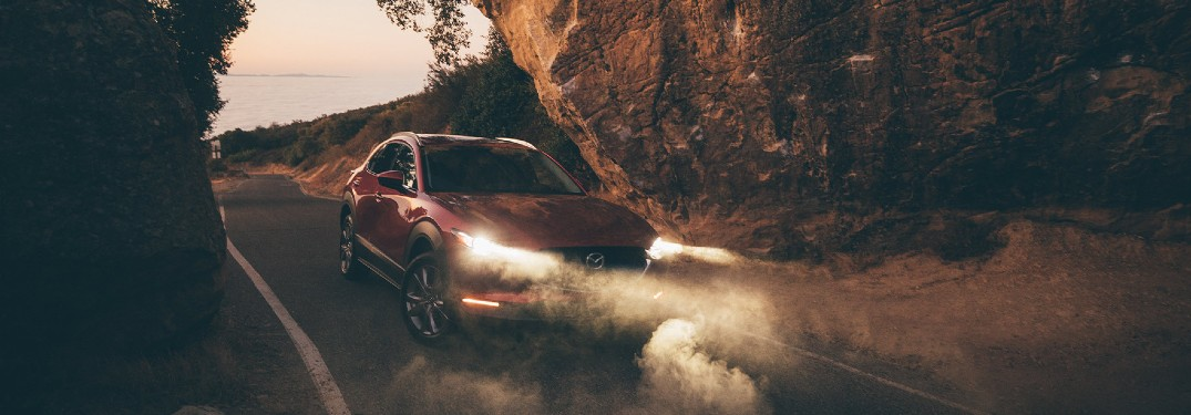 A red 2020 Mazda CX-30 driving between two large rocks in a foggy atmosphere.