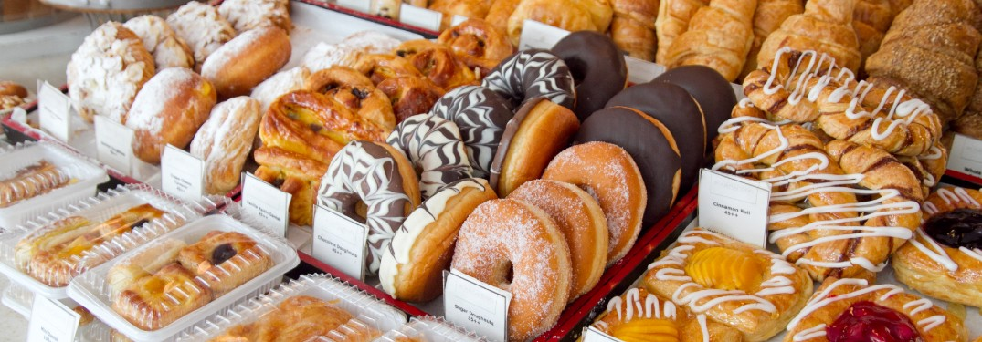 An image of baked goods, such as donuts and turnovers, at a bakery.