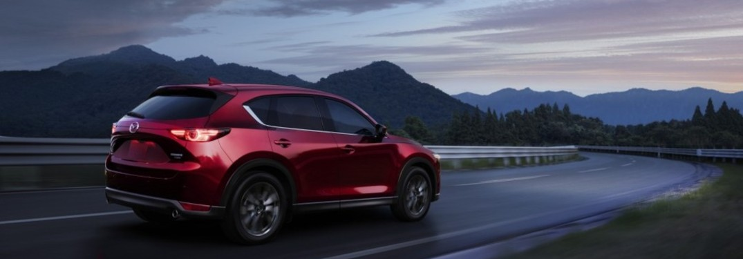 A red 2021 Mazda CX-5 driving down a road in the evening.