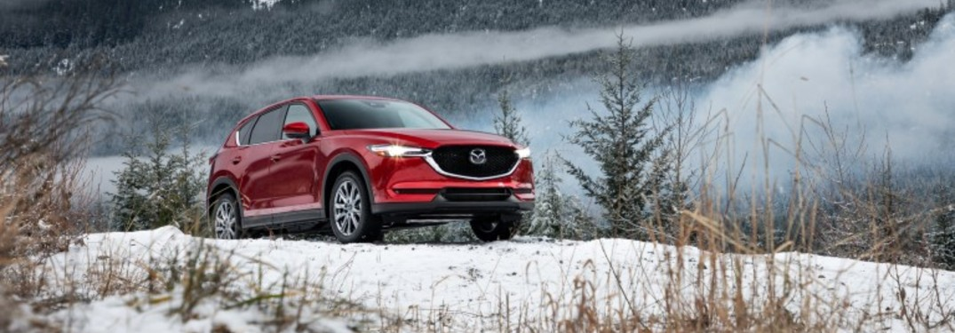 The front view of a red 2019 Mazda CX-5 parked on a wintry hill.
