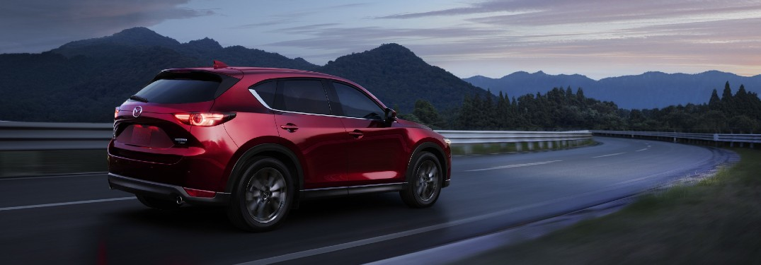The rear and side view of a red 2021 Mazda CX-5 driving on an open road at dusk.