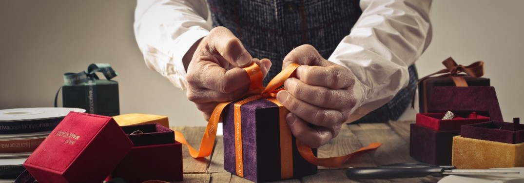 AN elderly man trying a bow to a present on a table.
