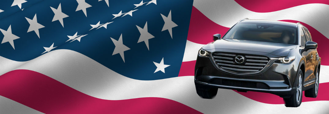 ... 2018 Mazda Cx 9 In Gray Driving In Front Of American Flag