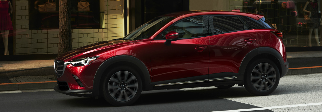 red 2019 mazda cx-3 driving down city street