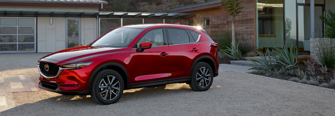 red mazda cx-5 in driveway of modern home