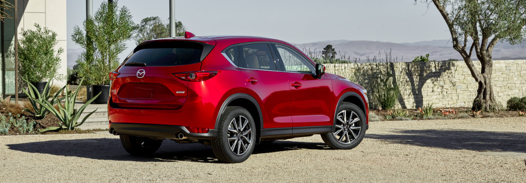 rear view of red 2018 mazda cx-5 in driveway of modern home