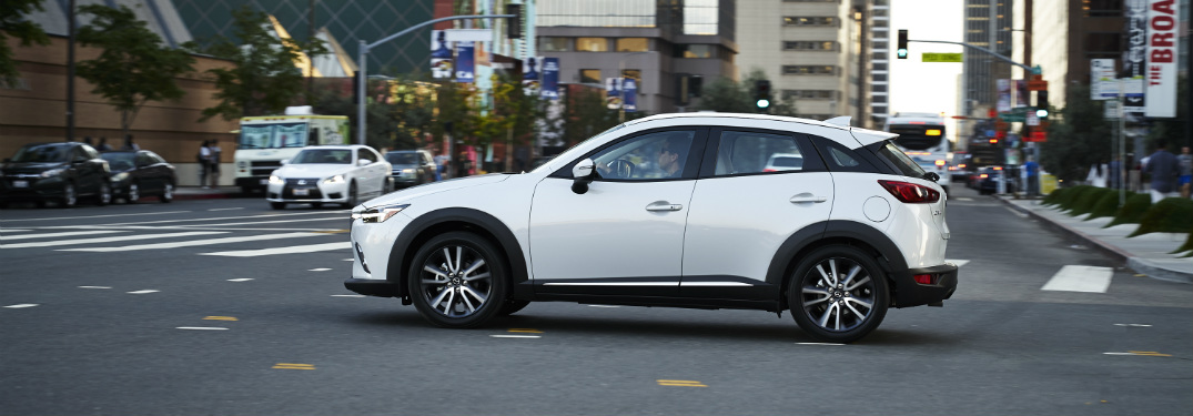 side view of white 2018 mazda cx-3 driving through intersection of downtown city