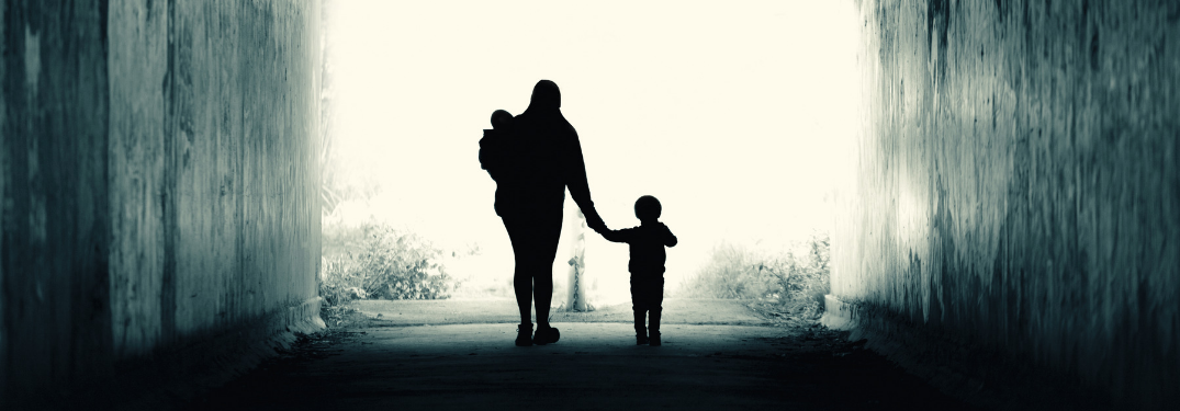 silhouette of woman walking with two children