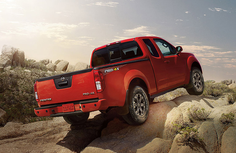Rear view of red 2018 Nissan Frontier pickup scaling up rocky hill
