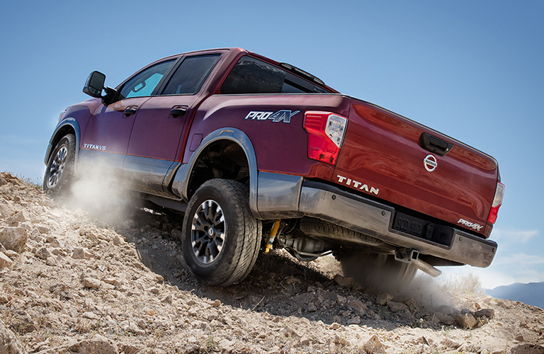 Rear view of red 2018 Nissan TITAN pickup driving up gravelly hill