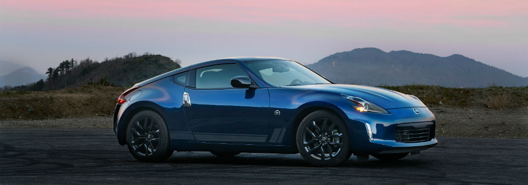 blue Nissan 370Z by some mountains at sunset