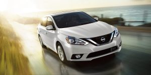 2018 Nissan Sentra driving past a field and water