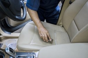 Close Up Of Worker Hand Using A Brush To Clean The Leather Car Seat And Remove