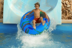 child going down a water slid in a tube