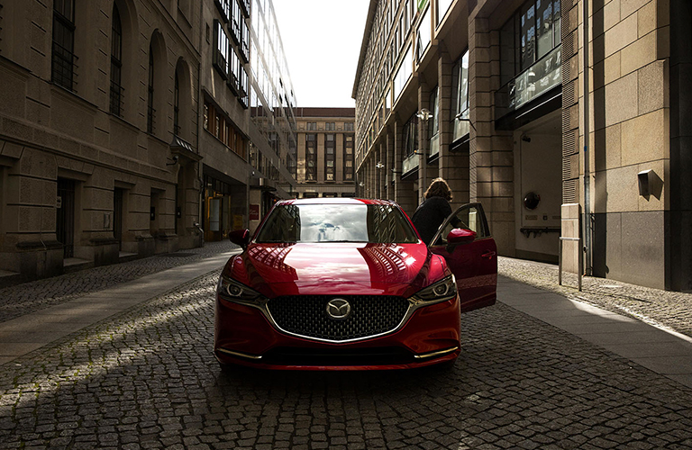 Individual exiting parked 2018 Mazda6 on cobblestone road