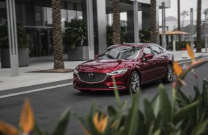 dark red mazda6 on road by flowers