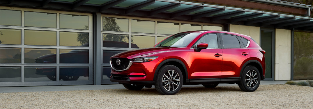left side view of red mazda cx-5 parked outside of glass garage door