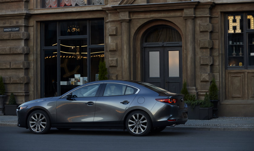 left side view of gray mazda3 parked on side of road