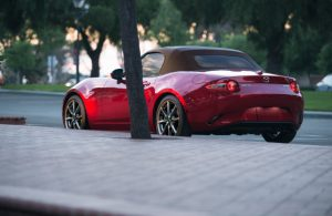 rear view of red mazda miata parked on side of road