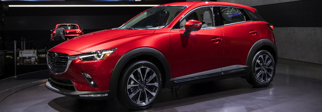 left side view of red mazda cx-3 on display