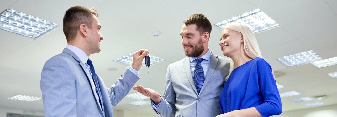 salesman handing keys to couple