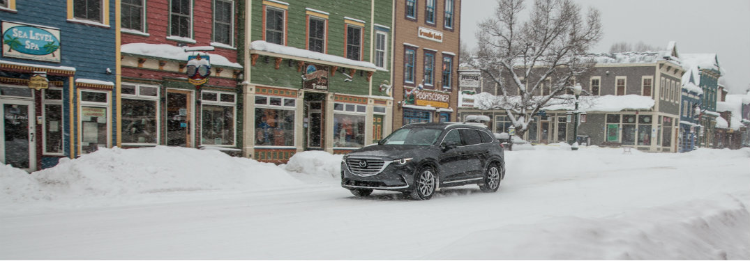 dark gray mazda driving on snow by buildings