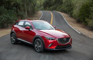 front-right view of red mazda cx-3 parked in middle of road