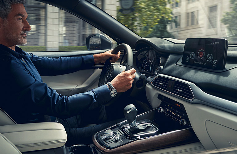 The interior view of a man driving a 2020 Mazda CX-9.
