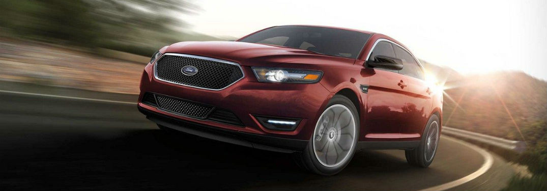 red 2018 Ford Taurus driving around a corner on a country highway