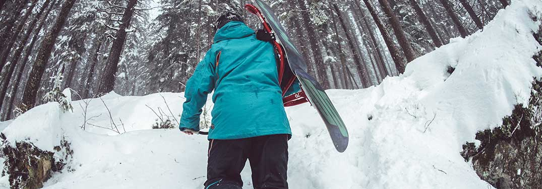 snowboarder climbing a snowy hill