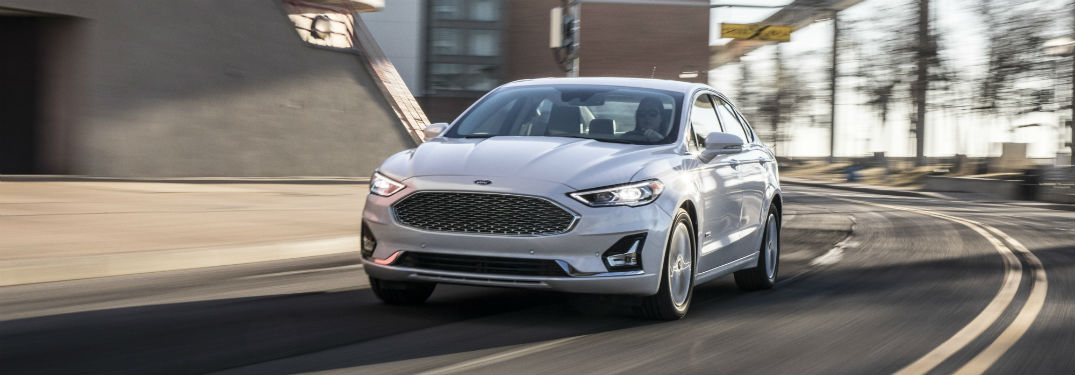 front view of a white 2019 Ford Fusion rounding a city curve