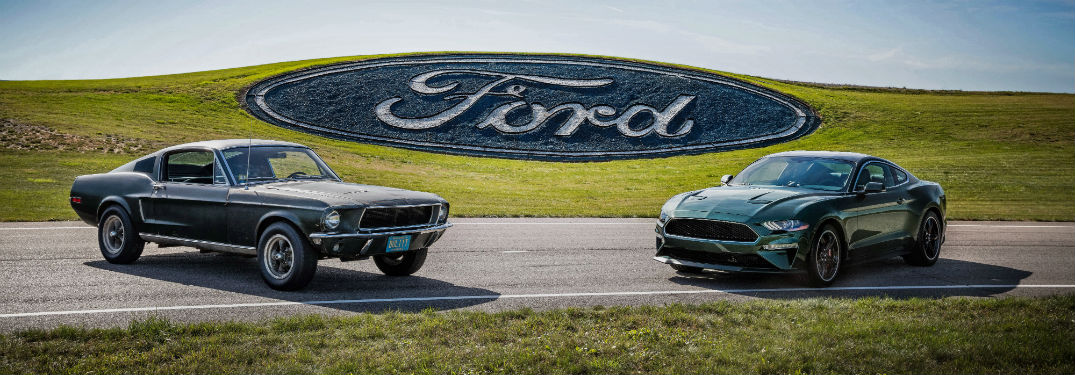 1968 Ford Mustang GT and 2019 Ford Mustang Bullitt parked next to each other with the Ford logo in the background