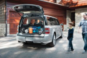 family loading up the back of their silver 2019 Ford Flex