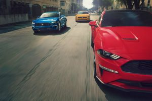 three 2019 Ford Mustangs driving alongside each other