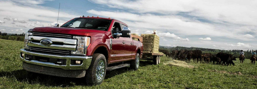 font view of a red 2019 Ford Super Duty towing a trailer full of hay