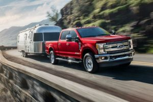 front view of a red 2019 Ford Super Duty towing a camper