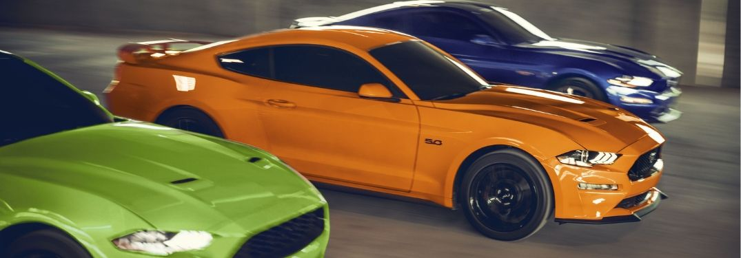 three 2020 Ford Mustangs racing down road