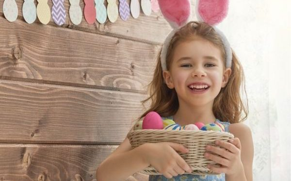 young girl with Easter eggs and bunny ears